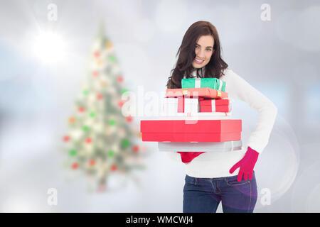 Jolie brunette posing and holding pile de cadeaux contre l'arbre de Noël floue dans la chambre Banque D'Images