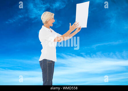 Femme en colère en criant à bout de papier contre le ciel bleu Banque D'Images