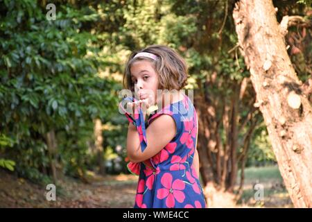 Portrait Of cute girl Blowing Kiss au Parc Public Banque D'Images