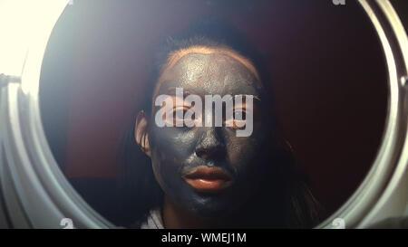 Femme avec masque de boue, reflétant sur miroir Banque D'Images