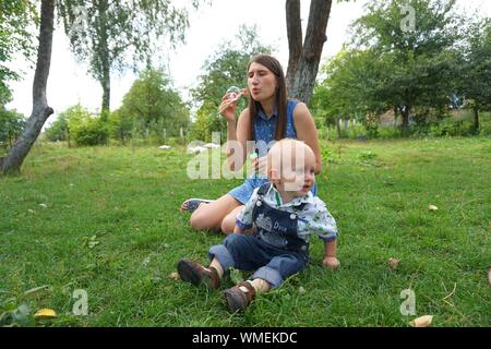 Bébé Garçon enjoué avec mère faire des bulles dans la cour arrière Banque D'Images