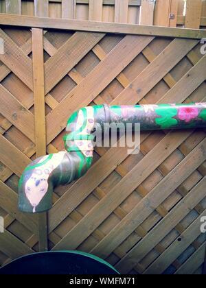 Tuyau décoré contre Fence Banque D'Images