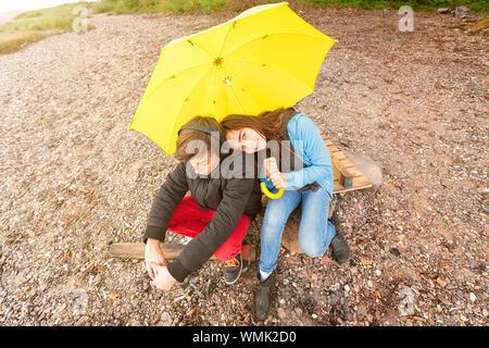 Portrait d'amis avec parapluie Sitting on Rock Banque D'Images