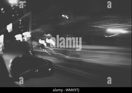 Des sentiers de lumière sur la vue à travers la fenêtre de voiture de nuit Banque D'Images