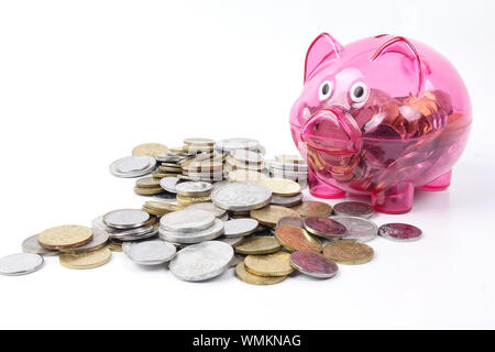 Close Up Of Pink Piggy Bank With Coins contre fond blanc Banque D'Images