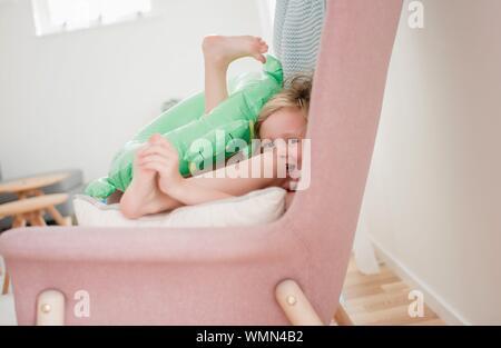 Jeune fille assise sur une chaise à la maison rire jouer avec ses jouets