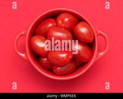 Tourné directement au-dessus des tomates dans un bol sur fond rouge Banque D'Images