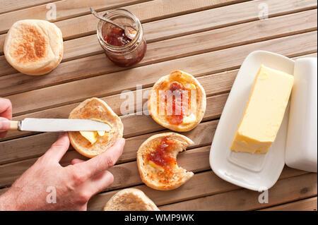 Beurrer un homme grillé fraîchement préparés pour le petit-déjeuner de crumpet une grande noix de beurre avec un pot de confiture ou de préserver, avec vue de dessus de son h Banque D'Images