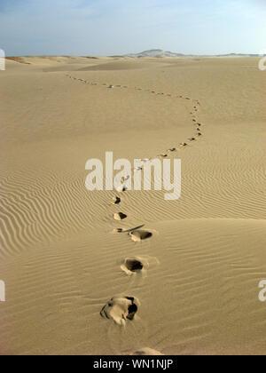 Empreintes de pas sur le sable dans le désert contre le ciel Banque D'Images