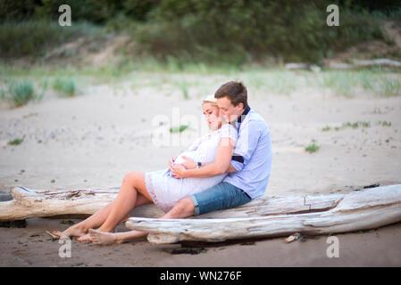 Homme assis avec femme enceinte sur Driftwood At Beach Banque D'Images