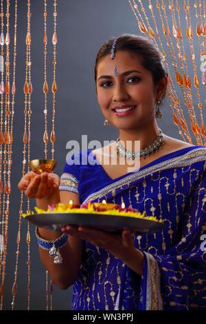 Magnifique Portrait de femme indienne en Sari Holding offrandes religieuses pendant Diwali