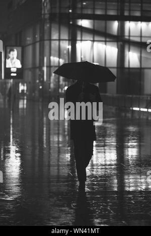 Homme marchant avec parapluie sur sentier dans la pluie de nuit Banque D'Images