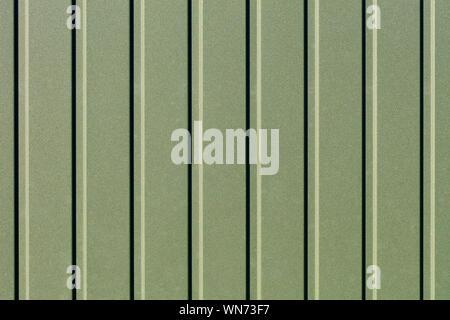 Clôture métallique verdure faite de tôle d'acier ondulée avec des guides verticaux. Fond d'fer vert ondulé close up. Banque D'Images