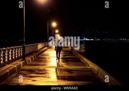 Vue arrière de l'homme marche sur la jetée humide illuminé contre Sky at Night Banque D'Images