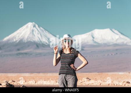 Jeune femme blonde occasionnels voyager seul, woman in hat and sunglasses looking at camera avec ses montagnes couvertes de neige sur l'arrière-plan. Superbe