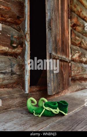 Elf créature féerique ou la forêt gauche naine ses chaussures sur le seuil d'une vieille maison de bois près de la porte