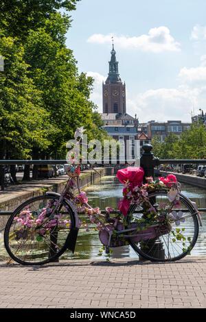 Parking vélo rose sur le pont sur l'eau calme d'un canal avec un bateau donnant un aller-retour pour les touristes, Amsterdam, Pays-Bas