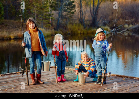 Quatre petites filles prendre du poisson sur un ponton en bois. La pêche avec des amis. Banque D'Images