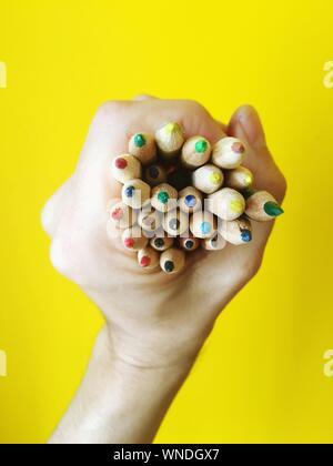Cropped Hand Holding Crayons de couleur contre fond jaune Banque D'Images
