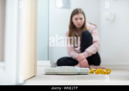 Malheureux Teenage Girl Sitting dans la salle de bains à la recherche, à des échelles et ruban à mesurer Banque D'Images