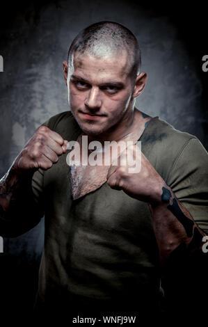 Portrait d'Homme debout en position de combat contre l'arrière-plan gris Banque D'Images