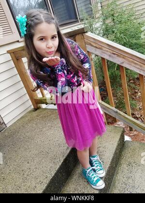 Portrait of Girl Blowing Kiss en se tenant sur le pas Banque D'Images