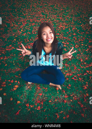 Portrait Of Smiling Woman Showing signe de paix au milieu de feuilles sur le terrain Banque D'Images