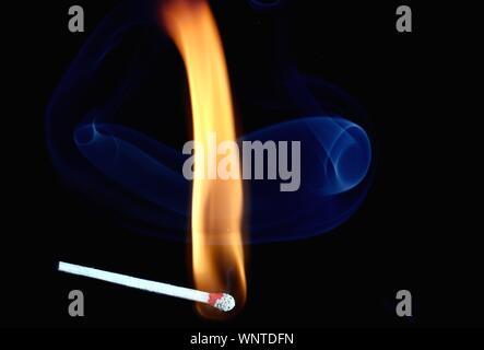 Close-up of Burning Match contre Fond noir Banque D'Images