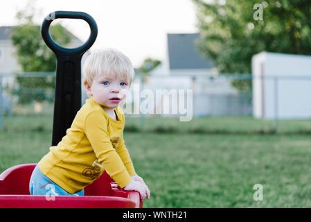 Bébé garçon debout dans un chariot rouge portant une chemise jaune. Banque D'Images