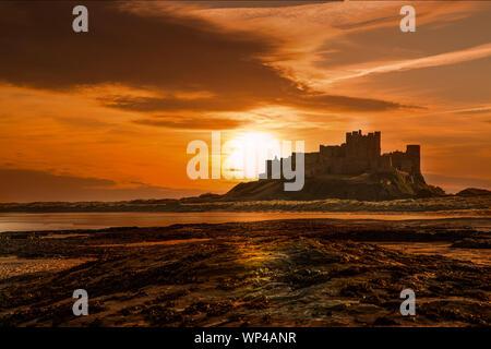 Lever du soleil sur le château de Bamburgh Northumberland Banque D'Images