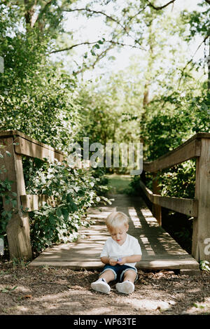 Mignon petit gamin Blond Bébé garçon enfant assis et de rire en face de pont de bois sur un ruisseau au parc dans la forêt en été
