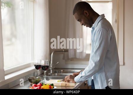 Smiling man biracial préparer un dîner romantique sur la cuisine Banque D'Images