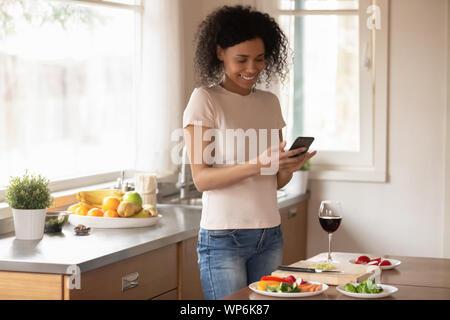 Smiling woman texting biracial cellule sur la préparation des aliments Banque D'Images