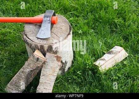 Fendre avec une hache et le fractionnement du bois de chauffage sur l'herbe. Grumes de bouleau