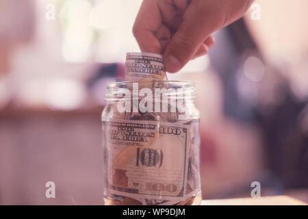 Place de l'argent dans la banque d'épargne en verre avec Banque D'Images