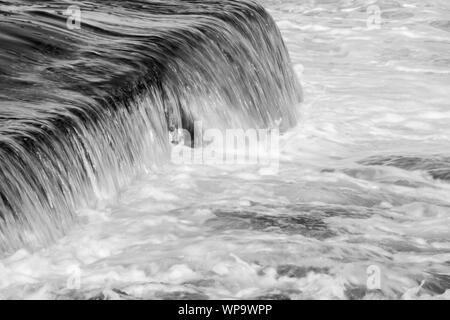 Abstrait noir et blanc des photographies d'un paysage marin avec de forts remous avec de l'eau coulant sur un bassin de marée mur à une faible vitesse d'obturation - puissant Banque D'Images