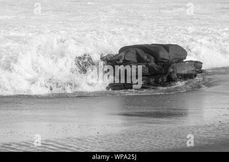 Un beau paysage marin noir et blanc avec des eaux sereines et mousse. Les vagues se fracassent contre un rocher en fin d'après-midi. Banque D'Images