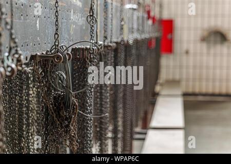 Close up groupe de petites chaînes suspendues à l'intérieur d'abandonner l'ancien bâtiment industriel ou d'usine. Détail de parties de machines, des chaînes pendent sur la partition. Banque D'Images