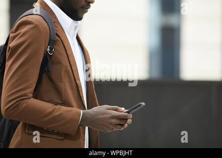 Mid section Vue de côté de l'homme afro-américain holding smartphone et la saisie des messages texte en milieu urbain, copy space