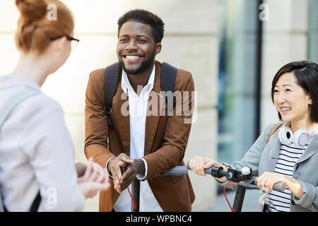 Groupe de jeunes contemporains bavarder dans la rue de la ville, l'accent sur l'homme afro-américain en souriant joyeusement, copy space