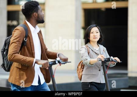 Taille portrait of Asian woman riding scooter électrique en street avec homme africain, copy space Banque D'Images