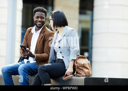 Portrait de deux jeunes gens d'affaires de détente en plein air pendant les pauses, l'homme africain et asiatique femme chat heureusement, copy space