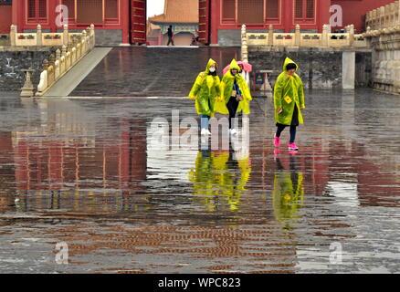 L'architecture traditionnelle chinoise de Cité Interdite porte du palais reflète l'eau de pluie sur les flaques, Beijing, Chine Banque D'Images