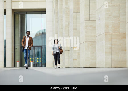 Longueur totale de portrai deux personnes marchant dans la rue de la ville, l'accent sur l'homme afro-américain équitation scooter électrique, copy space