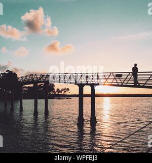 L'homme silhouette sur la passerelle au-dessus de mer contre Sky pendant le coucher du soleil Banque D'Images