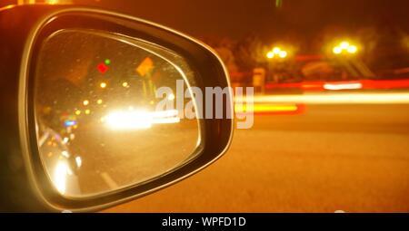 La réflexion de la lumière des sentiers sur rétroviseur de nuit Banque D'Images