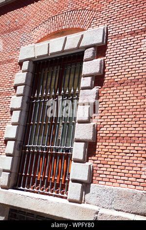 L'ancienne fenêtre avec caillebotis et mur de briques rouges Banque D'Images