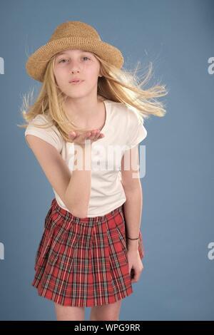 Portrait of Teenage Girl Wearing Hat Blowing Kiss contre fond bleu Banque D'Images