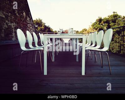 Chaises blanches à table à manger sur la terrasse Banque D'Images