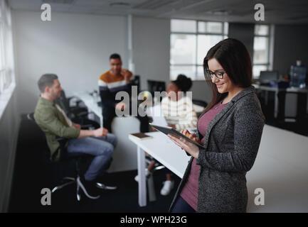 American Businesswoman using digital tablet par 24 avec des collègues discutant en arrière-plan à l'entrepreneur démarrage d'office